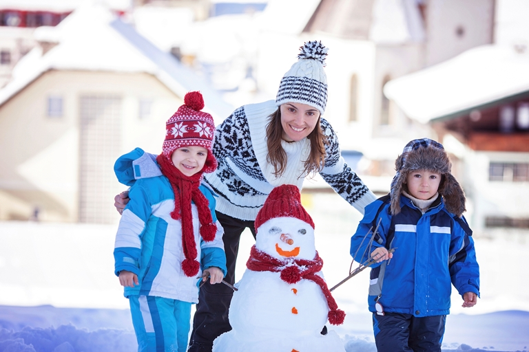 Happy beautiful family building snowman in garden, winter time, mom and kids
